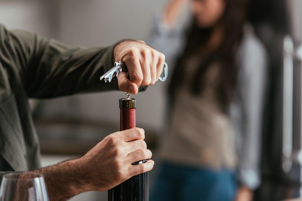 Mand der åbner en flaske vin med en vinoplukker